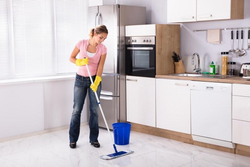 donna pulisce pavimento cucina