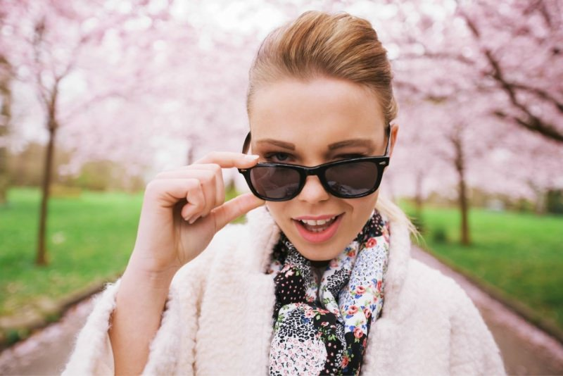 giovane donna sveglia fa l'occhialino occhiali da sole alberi fiori rosa ciliegio