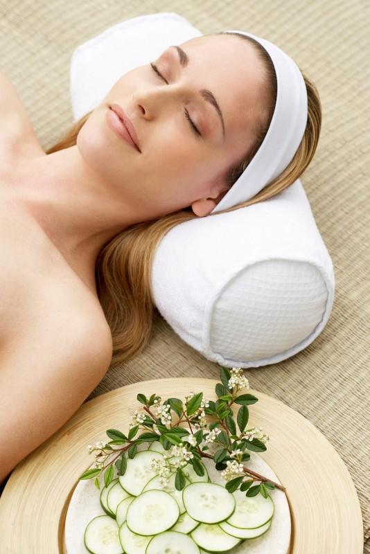 Viso donna bellissima testa su cuscino fettine cetriolo su piatto relax