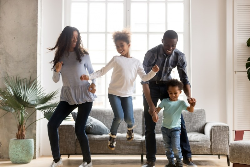 famiglia felice allegra sorridente balla salotto di casa