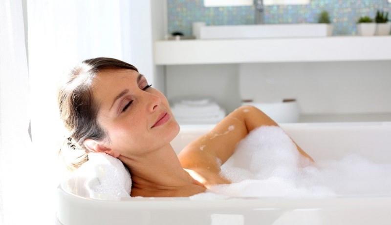 Come ridurre il gonfiore addominale vasca relax bagno donna rilassata capelli castani occhi chiusi schiuma