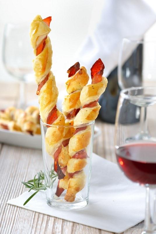 grissini di pasta sfoglia prosciutto crudo nel bicchiere tavola apparecchiata calici vino rosso