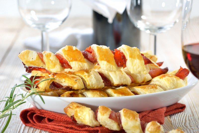 grissini di pasta sfoglia prosciutto crudo vassoio su tavola apparecchiata festa calici