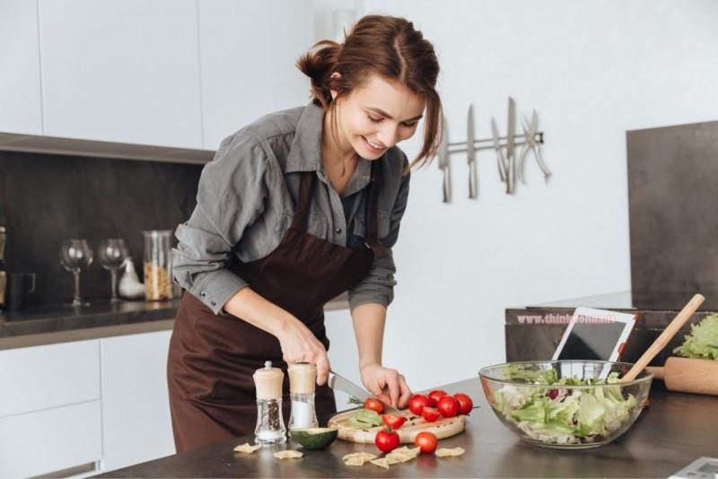 giovane donna impara a cucinare taglia pomodoro coltello tagliere hobby passatempo restare a casa