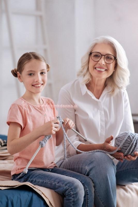 bambina sorriso impara a lavorare a maglia ferri insegnante nonna restare a casa hobby passatempo