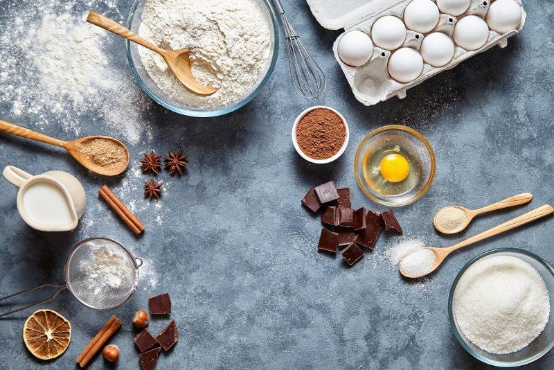 ingredienti per brownies ciotola farina mestolo legno zucchero uova latte cioccolato nocciole