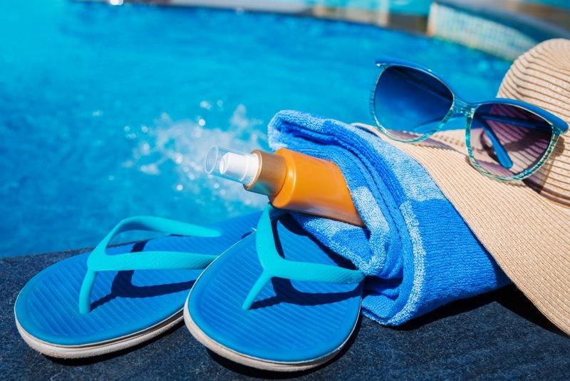protezione solare piscina estate telo spugna infradito cappello di paglia flacone lozione solare occhiali da sole