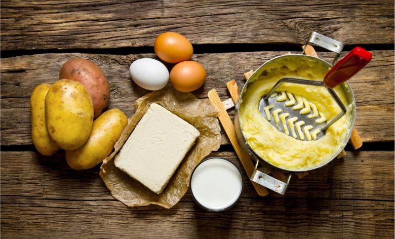 pentola purè patate schiacciapatate uova burro su tavolo legno ingredienti