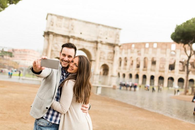 innamorati fanno selfie uomo donna coppia sorriso davanti colosseo roma
