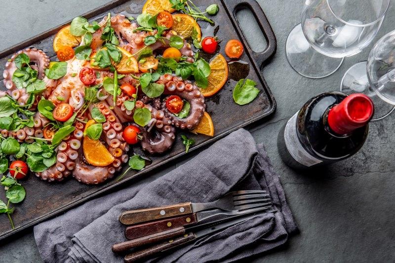 insalata di polpo con arance pomodorini e crescione bottiglia calici bicchieri vino rosso