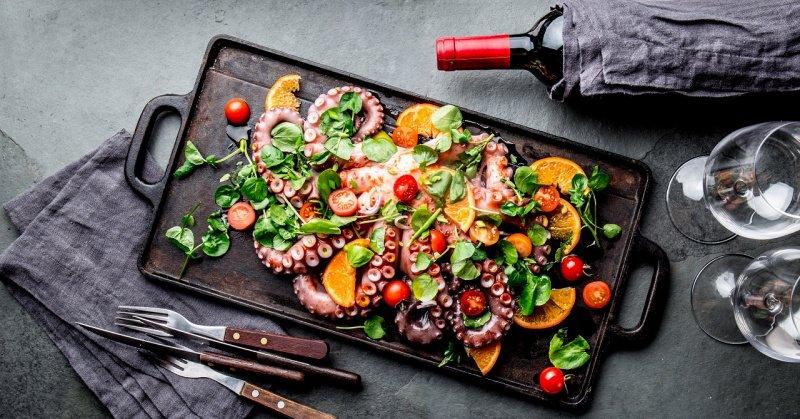 insalata polpo arance pomodorini foglie di crescione vassoio posate coltello forchetta bottiglia vino rosso calici
