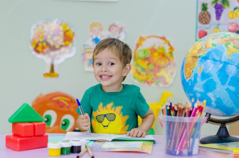 compiti per le vacanze bambino sorriso studio mappamondo colori