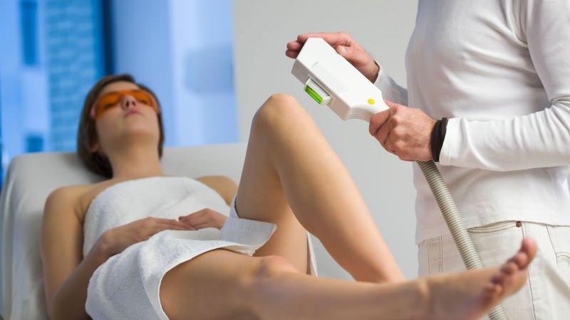 Depilazione al laser, sfatiamo i falsi miti! donna lettino telo bianco occhiali protezione