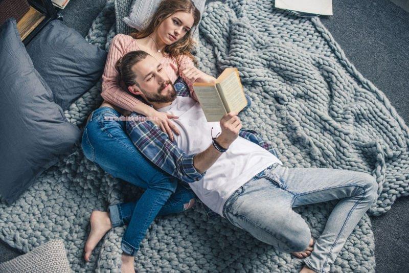 giovane donna sdraiata uomo coppia leggere lettura libro coperta fatta a i ferri hobby restare a casa