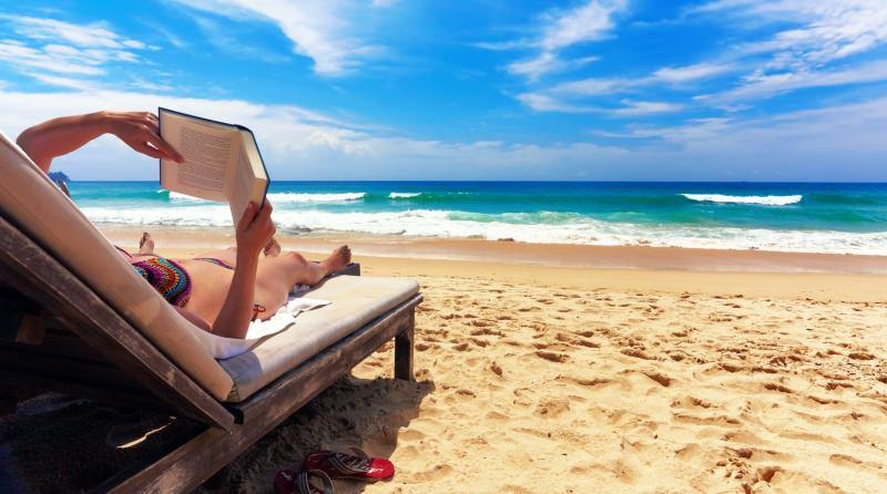 Estate, libri da leggere sotto l'ombrellone donna bikini all'uncinetto colorato legge libro sdraio spiaggia mare onde infradito sabbia