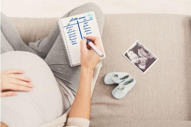 donna mamma con pancione incinta scrive lista nomi figlio nascita