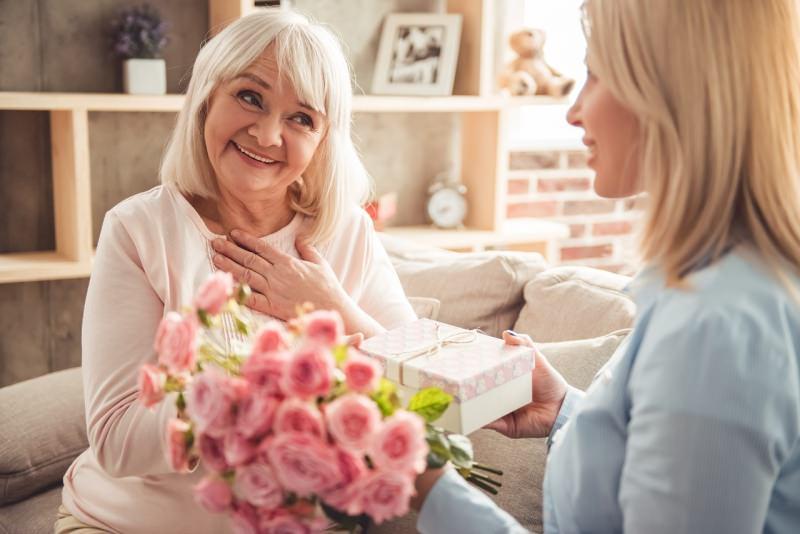 figlia adulta regala fiori alla madre signora anziana sorrisi festa della mamma