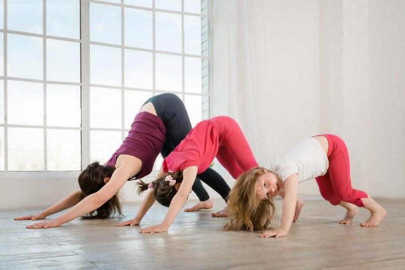 mamma e figlie fanno yoga in casa