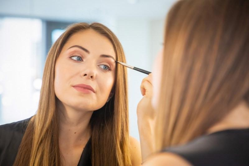 bella donna si mette il trucco make-up allo specchio pennello makeup occhi azzurri