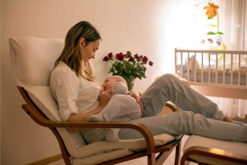 cameretta bambini nursery donna tieni in braccio suo figlio durante allattamento al seno