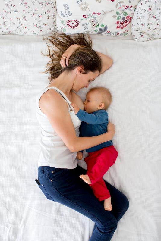 donna sdriata di fianco sul letto allattamento al seno bambino pochi mesi cuscini a fiori