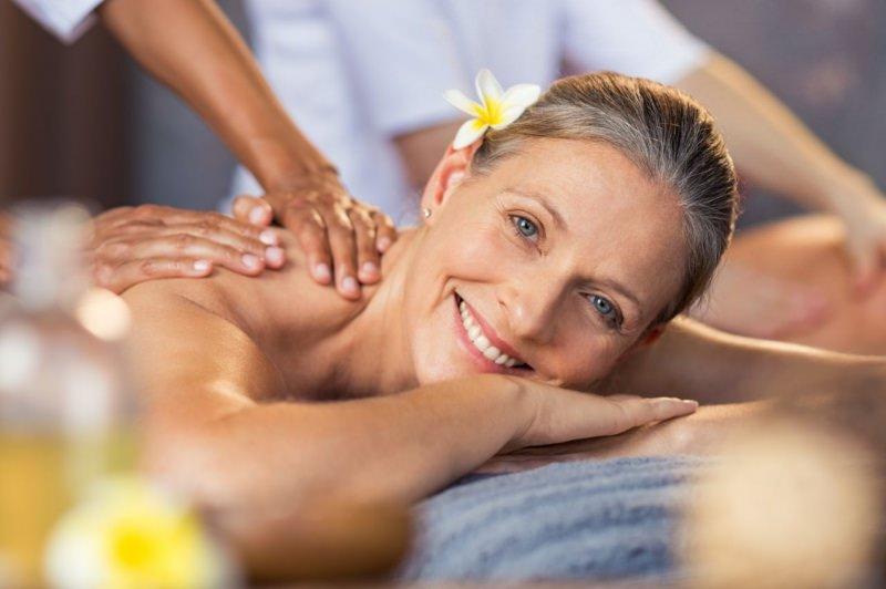 donna anziana si fa massaggio SPA fiore tiarè