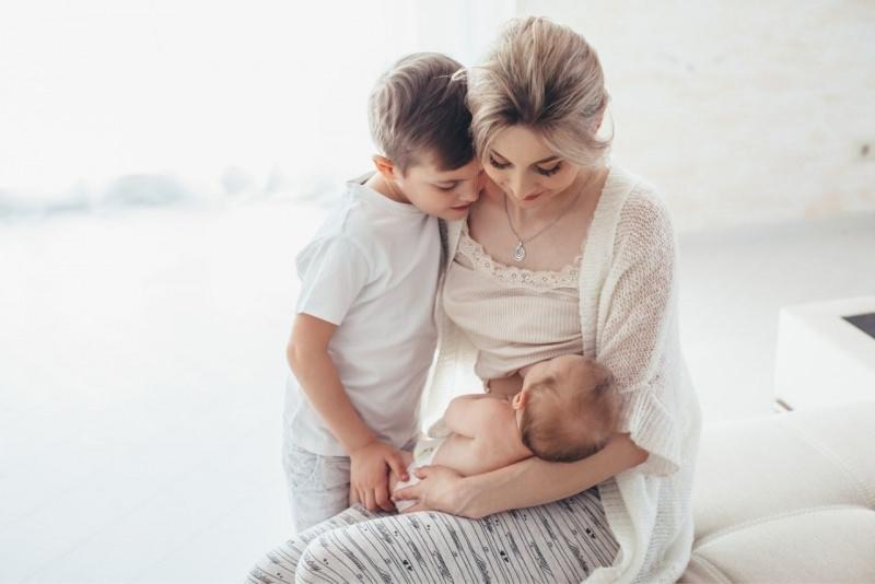 mamma con figli allatta neonato serenità