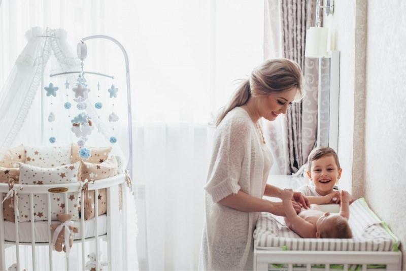 mamma sorridente cambia pannolino neonato nella nursery con figlio primogenito culla