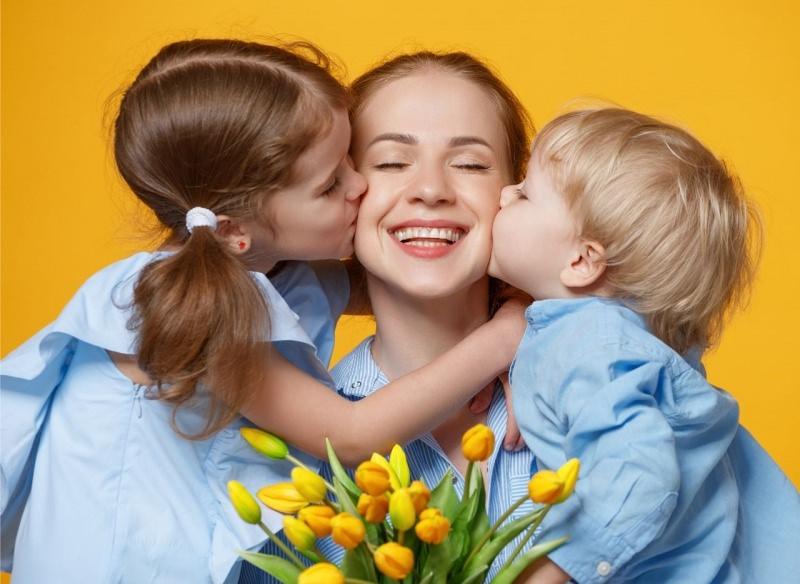 sorriso mamma baciata dai figli bambino bambina tulipani gialli bacio festa della mamma