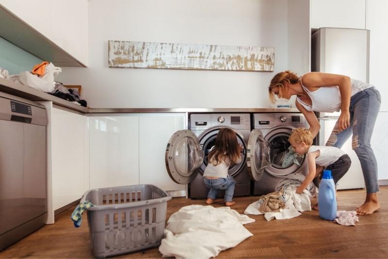 mamma insegna figli bambina bambino lavatrice asciugatrice bucato lavanderia