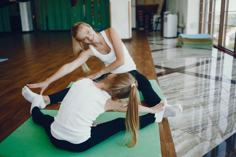 mamma e figlia fanno fitness in casa parquet soggiorno esercizi fisici