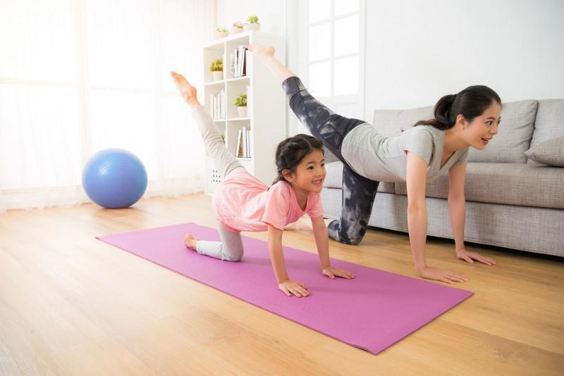 mamma e figlia fanno fitness esercizi fisici in casa tappeto divano