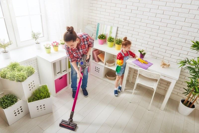 mamma e figlia fanno le pulizie in casa soggiorno aspirapolvere mobili