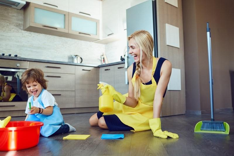 mamma e figlio si divertono facendo pulizie pavimento secchio spugna