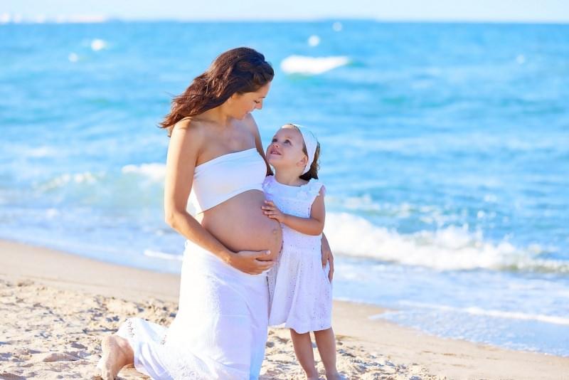 mamma incinta con figlia sulla sabbia spiaggia mare estate