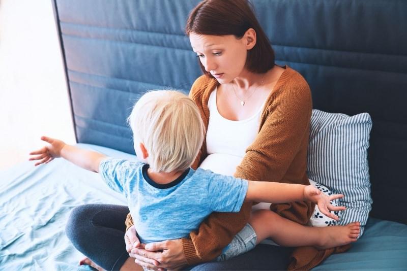 mamma incinta secondo figlio parla e tranquillizza primogenito abbraccio