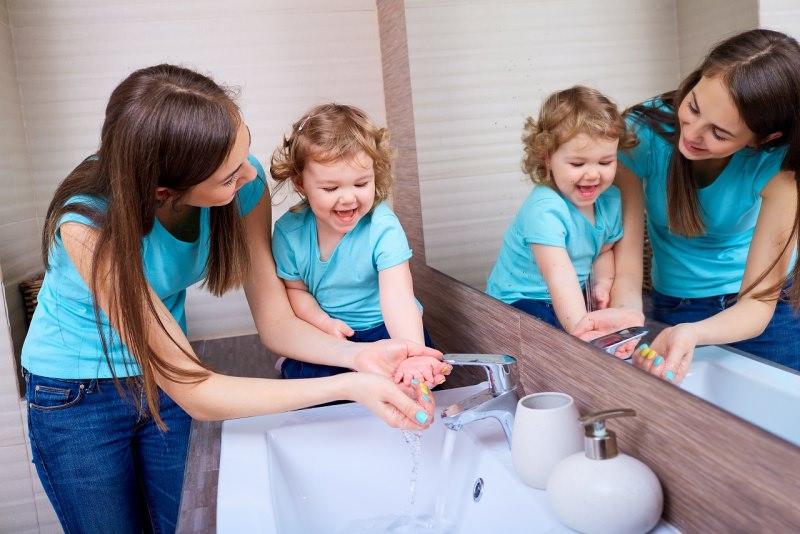 mamma e figlia specchio bagno giocano sorrisi lavarsi le mani