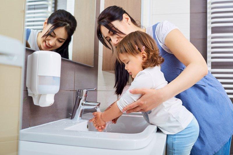 giovane mamma sorride mentre lava mani figlia bambina specchio bagno