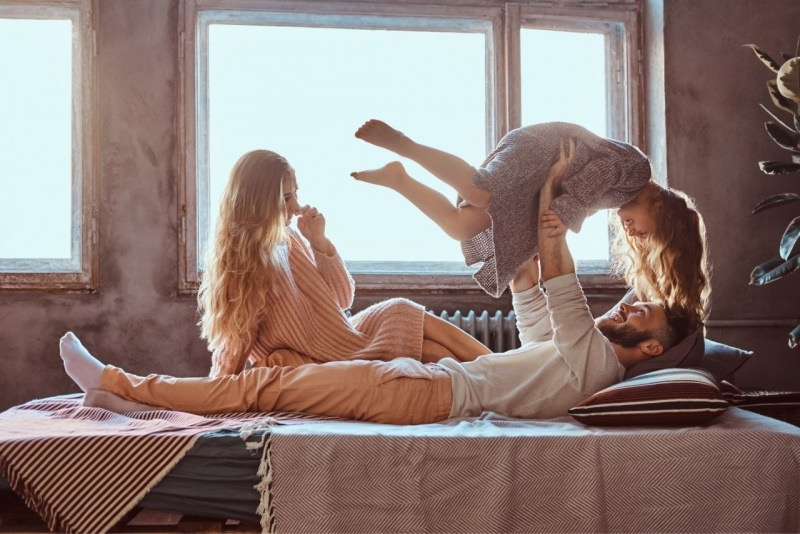 mamma papà e figlia giocano sul letto coccole e affetto