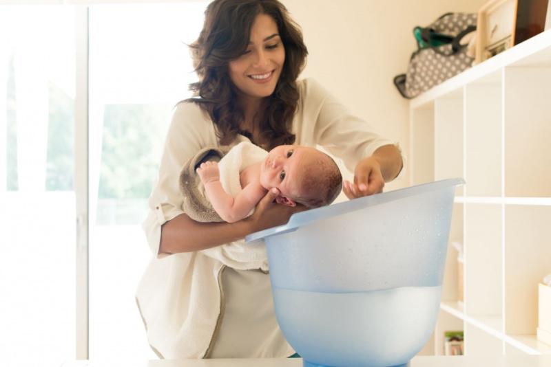 giovane donna mamma tiene in braccio figlio neonato e gli bagna la testa bagnetto