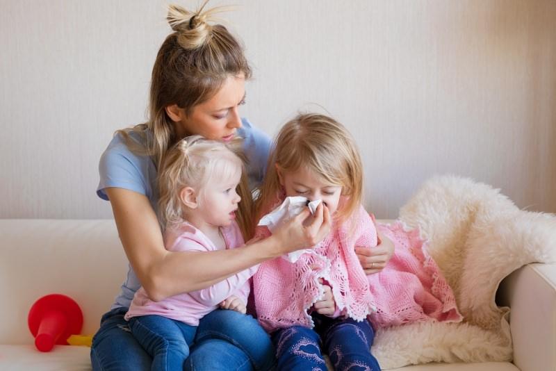 mamma si prende cura della figlia bambina raffreddore soffia naso bimba piccola guarda medicine