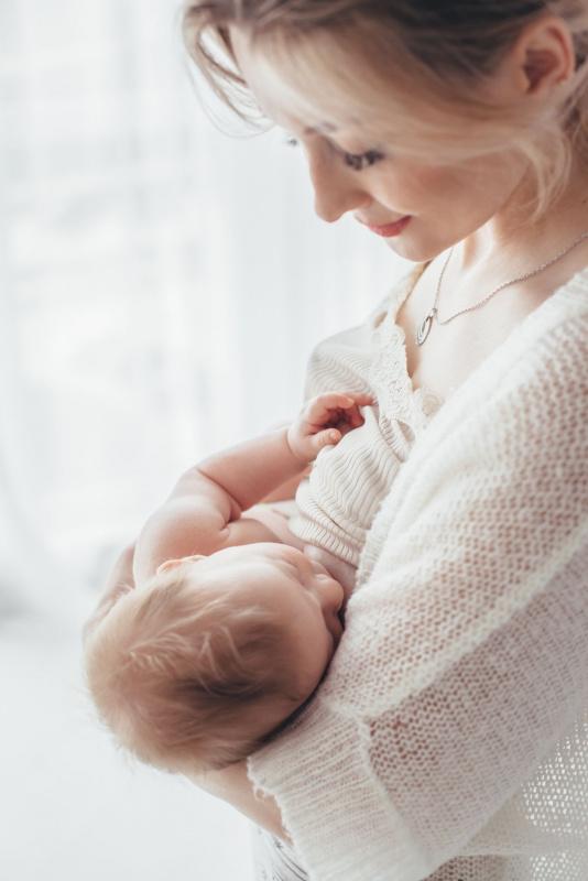 donna capelli biondi guarda figlio che tiene in braccio durante allattamento al seno