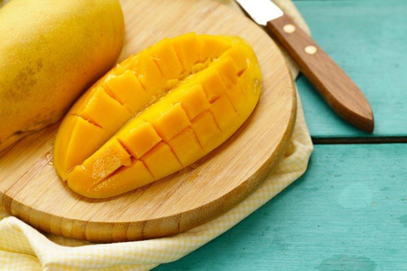mango tagliato a pezzi su tagliere coltello