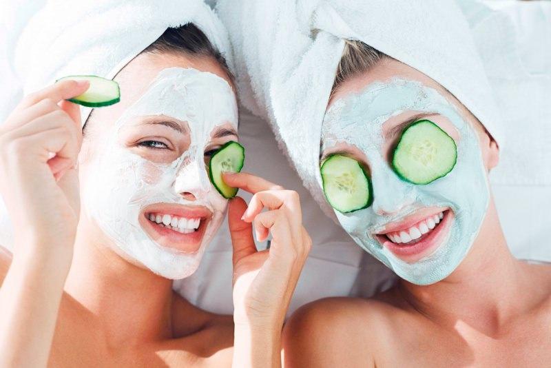 3 maschere da usare in estate dopo il sole viso ragazze sorridenti donna capelli castani sorriso denti bianchi maschera di bellezza verde fetta cetriolo occhi chiusi turbante spugna bianca