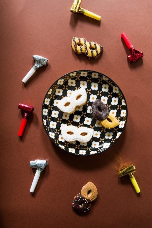 dolci di carnevale a forma di maschere zucchero a velo fischieti