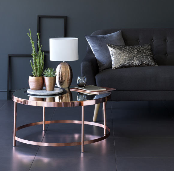 Arredamento: vivere con stile il moderno soggiorno divano grigio cuscino velluto azzurro maculato tavolo rame lucido piano specchio lume paralume bicchiere libri vasi piante grasse