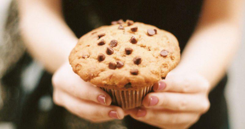 Muffin con gocce di cioccolato dolce mani donnaunghie smalto rosa antico