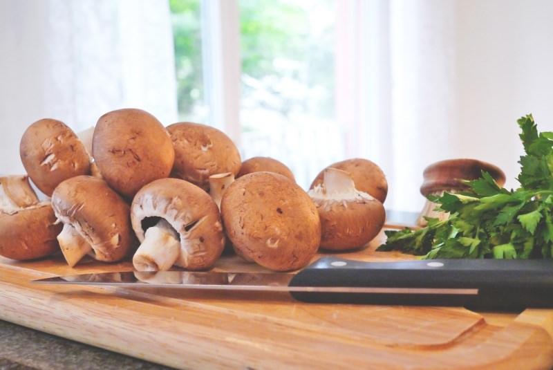Menu di Natale Antipasti | Funghi ripieni di verdure champignon coltello prezzemolo tagliere