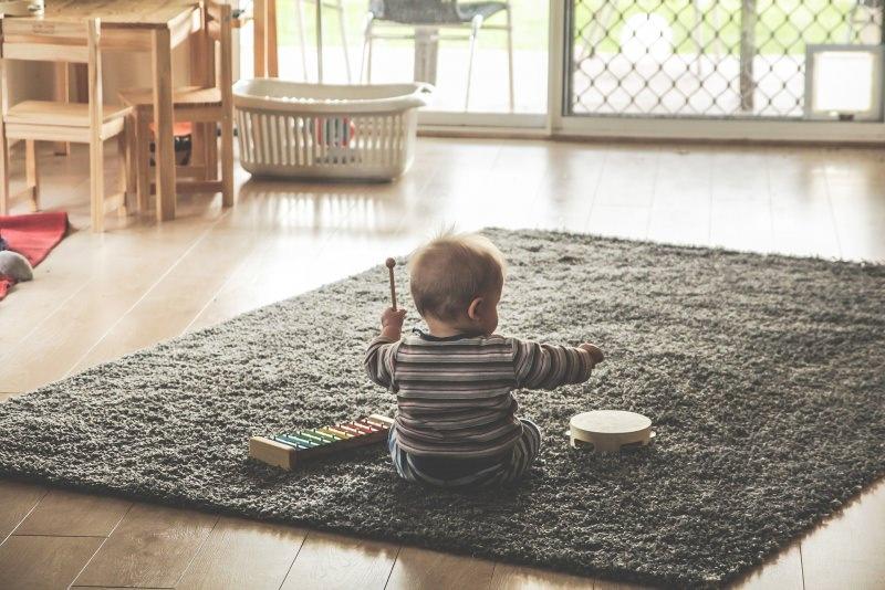 bambino piccolo gioca strumenti musicali xilofolo tamburello tappeto