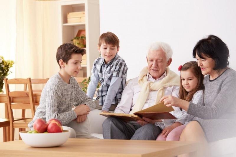 nonni leggono con i nipoti bambini in soggiorno divano